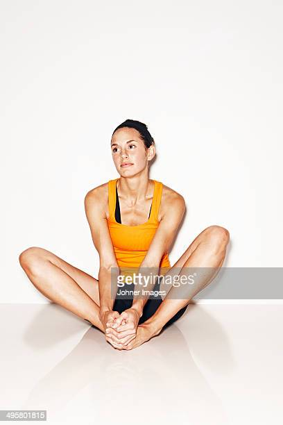 Woman in workout clothes sitting on floor