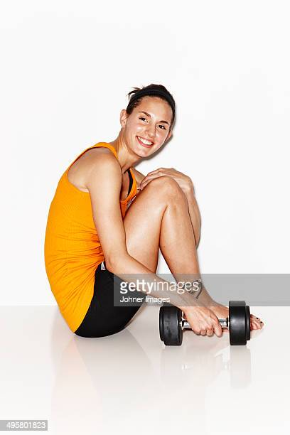 Woman in workout clothes with weight on white background