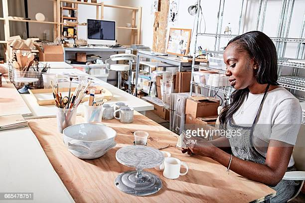 Woman in workshop painting pottery