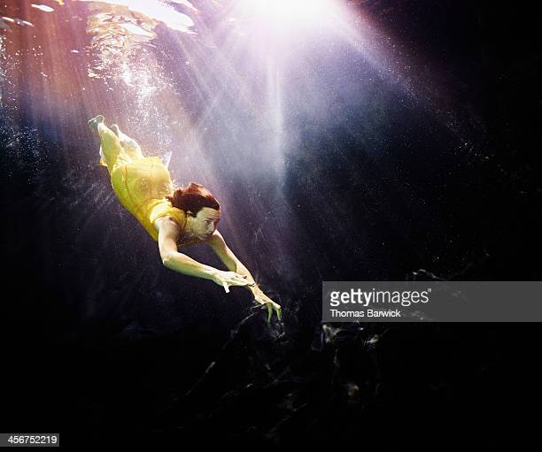 Woman in yellow dress diving underwater