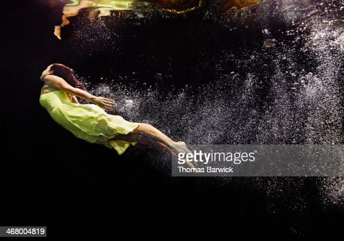 Woman in yellow dress swimming to water surface : Stock Photo