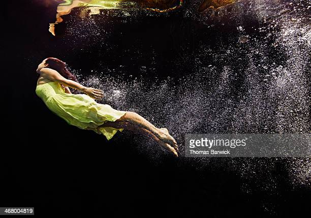 Woman in yellow dress swimming to water surface