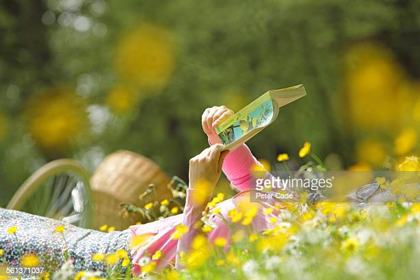 woman in yellow flower field reading a book.