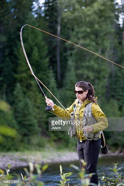 Woman in yellow jacket casting a fly rod in lake