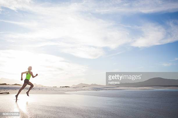 Woman in yellow running early morning on the beach