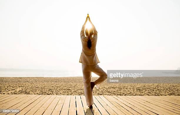 Femme dans la pose de yoga sur la plage