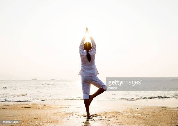 Woman in yoga pose at beach