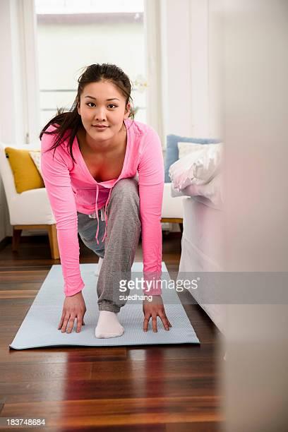 Woman in yoga pose looking at camera
