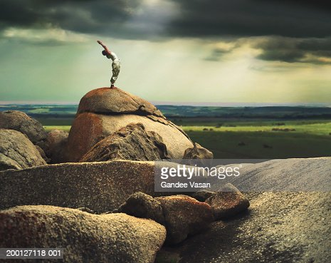 Woman in yoga pose on rock formation, side view (Digital composite) : Stock Photo