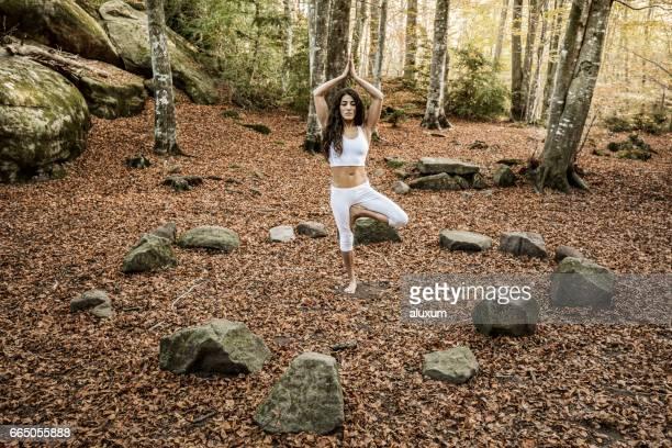 Femme dans l'arborescence d'yoga posent à l'intérieur du cercle de Pierre
