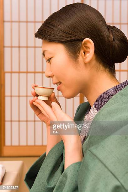 Woman in Yukata drinking Sake, side view, Japan
