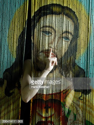 Woman indicating 'quiet' through beaded curtain with image of Jesus : Stock Photo