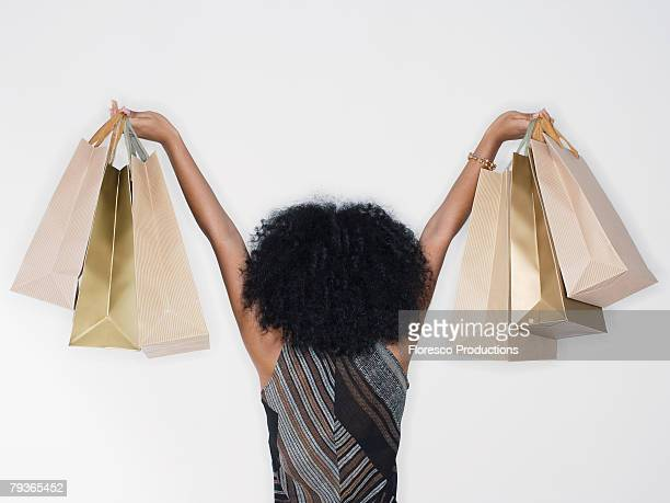 Woman indoors holding up shopping bags
