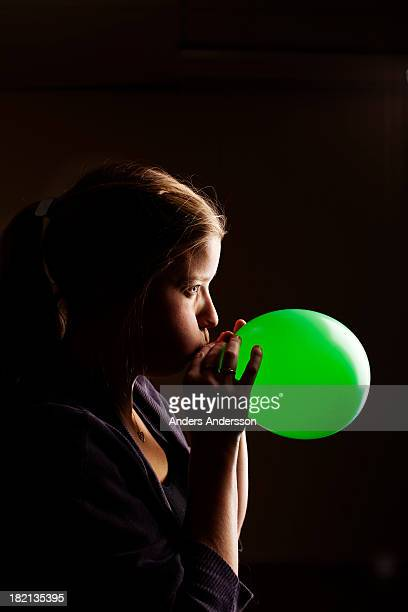 Woman inflating ballon