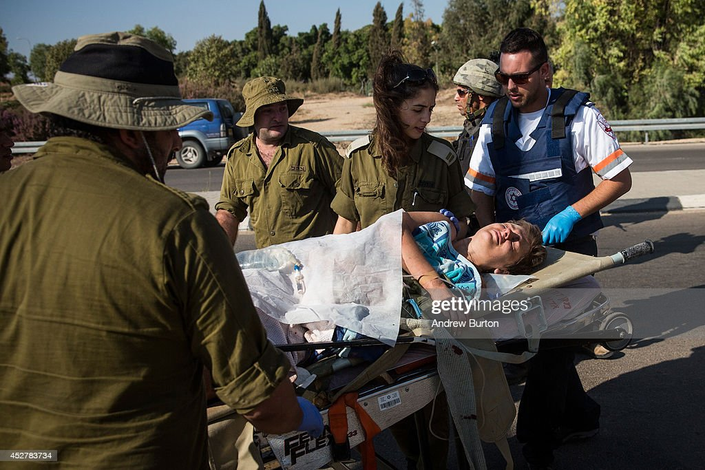 A woman injured in a rocket attack is transferred from a military ambulance to a civilian ambulance on July 27, 2014 near Nahal Oz, Israel. The nearly three week conflict has left more than 1,050 Palestinians dead. In Israel, 46 have died, including 43 soldiers, two civilians and a Thai worker.