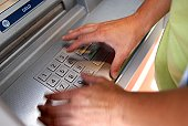 Woman inputting pin into atm machine