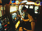 Woman inserting coin into slot machine in casino, man standing beside