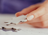 Woman inserting jigsaw piece, Close-up of hand