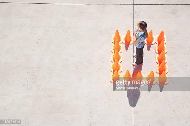 Woman inside box of traffic cones