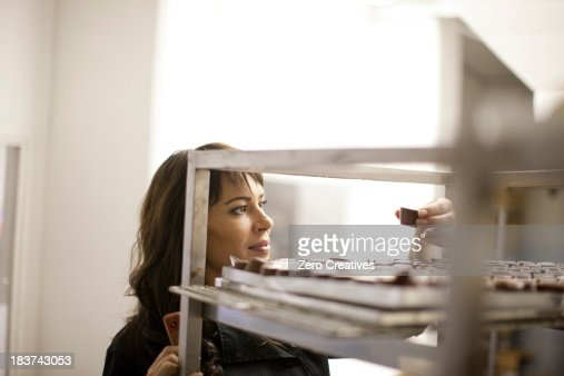 Woman inspecting chocolate in commercial kitchen