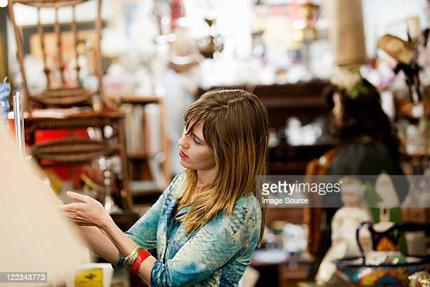 Woman inspecting items for sale in antiques shop