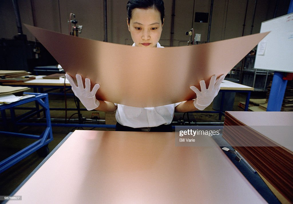 Woman inspecting sheet metal