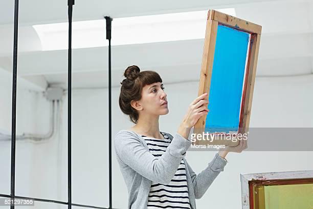 Woman inspecting silk screen