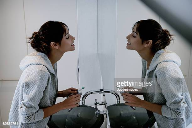 Woman inspecting smile in bathroom mirror