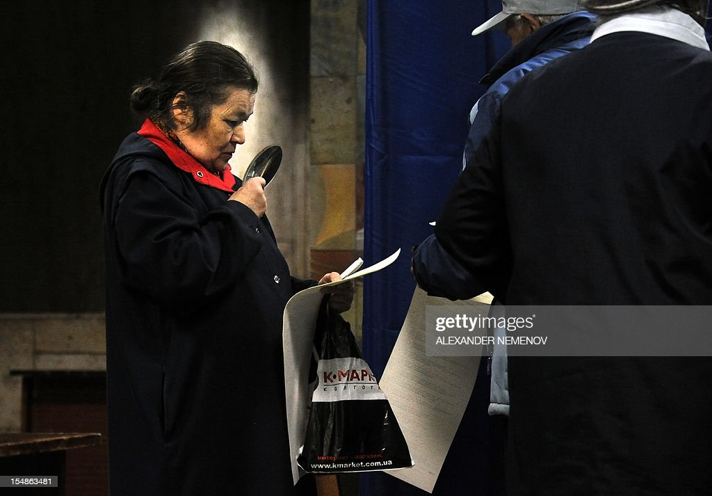 A woman inspects a ballot with the help of a magnifying glass at a polling station in Kiev on October 28, 2012, during national parliamentary elections. Ukraine voted today in legislative polls seen as a test of democracy under President Viktor Yanukovych with jailed opposition leader Yulia Tymoshenko forced to watch from the sidelines.
