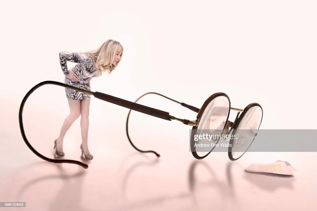 Woman inspects a document through giant spectacles