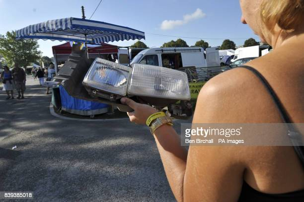 A woman inspects a headlight for a VW Type 25 Transporter she has bought in the trade stands area at Vanfest festival in the Three Counties...