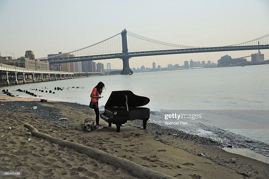 A woman inspects a piano underneath the Brooklyn Bridge on June 3, 2014 in New York City. A grand piano that has mysteriously landed on a sliver of beach under the iconic bridge last week has become an impromptu tourist attraction. While the Mason & Hamlin piano is badly damaged, dozens of people climb onto the beach daily to test out the keys.