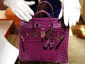 A woman inspects Hermes crocodile skin bag in Taipei on April 10 2009 French luxury goods group Hermes hailed a Taiwan court's ruling to impose a...
