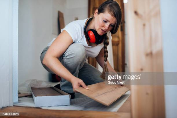 Woman installing laminate flooring.