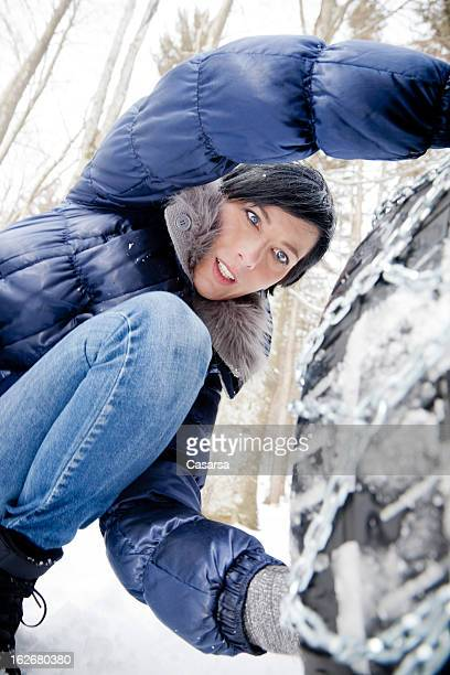 Woman installing snow chains