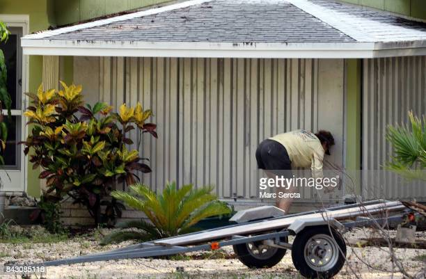 A woman installs hurricane shutters on her home in the Florida Keys on Septeber 5 2017 in Islamorada Florida Residents are evacuating ahead of...