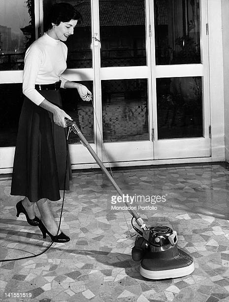 A woman intent on cleaning the floor with the polisher equipped with a spray with wax and vacuum cleaner 1960s