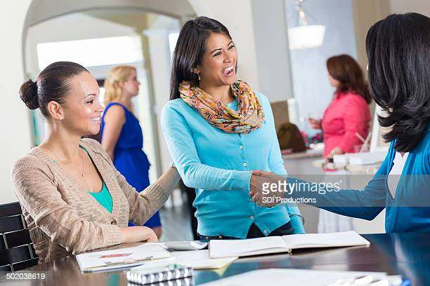 Woman introducing friend to lady at a home party