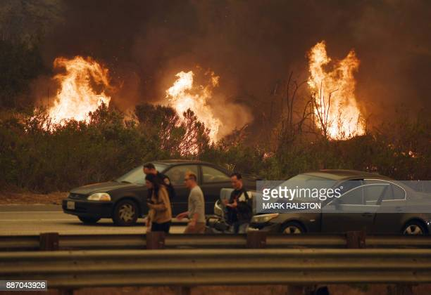 TOPSHOT A woman involved in a traffic accident waits to get towed beside a wall of flames on the 101 highway during the Thomas wildfire near Ventura...