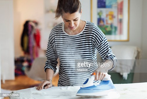 Woman ironing cloth in house