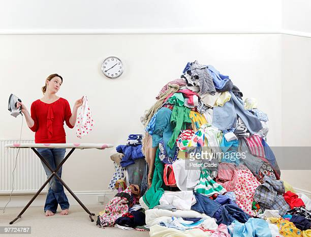 woman ironing next to very large pile of clothes