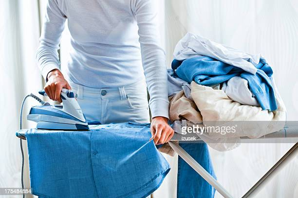 Woman Ironing Shirt Next To Pile Of Laundry