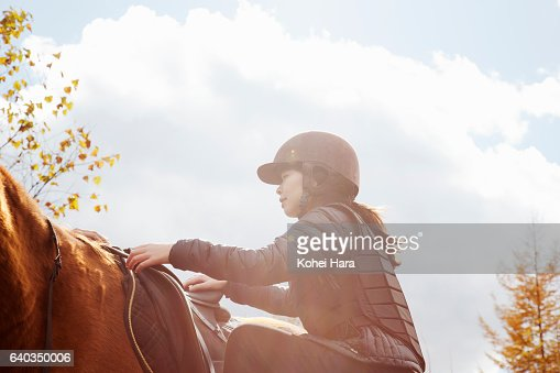 Woman is about to ride on horse in pasture