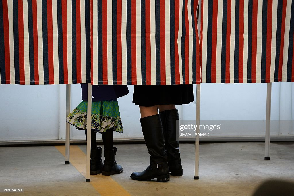 A woman is accompanied by a child inside a booth as she votes for the first US presidential primary at a fire station in Loudon, New Hampshire, on February 9, 2016. New Hampshire began voting on February 9 in the first US presidential primary with Republican Donald Trump calling on supporters to propel him to victory and Democrat Bernie Sanders primed to upstage Hillary Clinton. The northeastern state, home to just 1.3 million people, sets the tone for the primaries and could shake out a crowded Republican field of candidates pitting Trump and arch-conservative Senator Ted Cruz against more establishment candidates led by Senator Marco Rubio. SAMAD