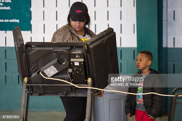 A woman is accompanied by a young child as she votes at McGee Community Center on March 1 2016 in Conway Arkansas / AFP / Michael B Thomas