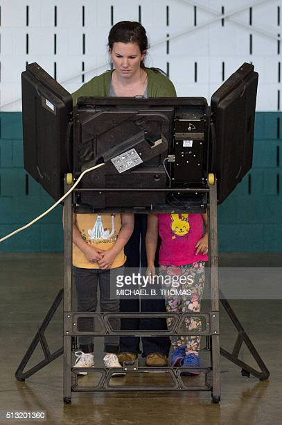 A woman is accompanied by two young children as she votes at McGee Community Center on March 1 2016 in Conway Arkansas / AFP / Michael B Thomas
