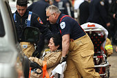 A woman is aided by New York City firefighters after being evacuated from an emergency staircase following an F train derailment on May 2 2014 in the...