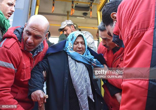 TOPSHOT A woman is assisted by members of the Syrian Arab Red Crescent after two buses evacuating civilians from Fuaa and Kafraya two Shiite villages...
