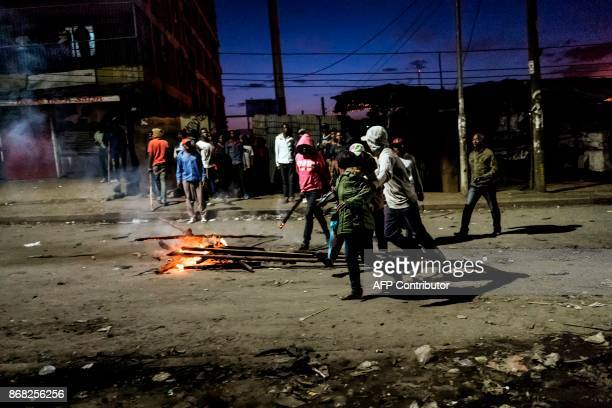 A woman is attacked buy opportunistic thugs while protesters gather around a burning barricade in the Mathare slums in Nairobi on October 30 2017...