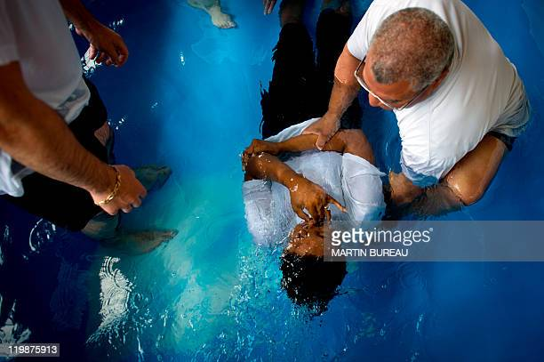 A woman is baptised during a Jehovah's Witnesses assembly gathering 30000 believers on July 23 2011 in Villepinte Paris suburb European rights judges...